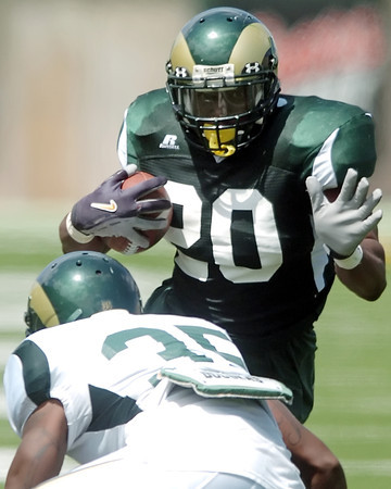 Colorado State University running back Raymond Carter makes a carry as defender Ivory Herd attempts to tackle him during a scrimmage on Saturday, Aug. 14, 2010 at Hughes Stadium in Fort Collins.