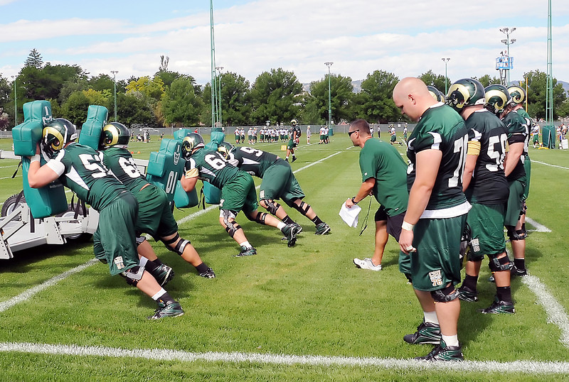 Colorado State University linemen push a training sled during football practice Thursday as offensive coordinator and offensive line coach Pat Meyer, center, runs them through the drill.