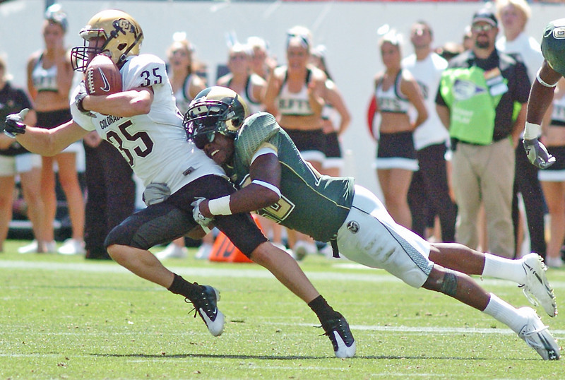 University of Colorado wide receiver Kyle Cefalo is tackled by Colorado State's Elijah-Blu Smith after making a catch during their game last September at Invesco Field in Denver.