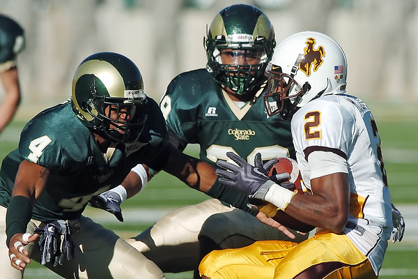 Colorado State University defenders Brandon Owens, left, and Broderick Sargent converge on Wyoming's Marcell Gipson in the third quarter of their game on Saturday, Nov. 27, 2009 at Hughes Stadium in Fort Collins. CSU lost, 17-16.