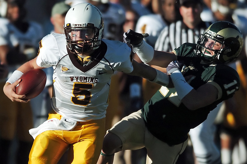 University of Wyoming quarterback Austyn  Carta -Samuels fends off Colorado State cornerback Nick Oppenneer on his way to the end zone for a touchdown in the fourth quarter of their game on Saturday, Nov. 27, 2009 at Hughes Stadium in Fort Collins. CSU lost, 17-16.