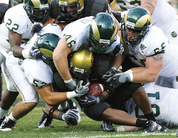 Colorado State defenders Michael Kawulok (52), Ty Whittier (46), and Guy Miller (66) take down Colorado tailback Demetrius Sumier (8) during the first half of the game at Folsom field in Boulder.