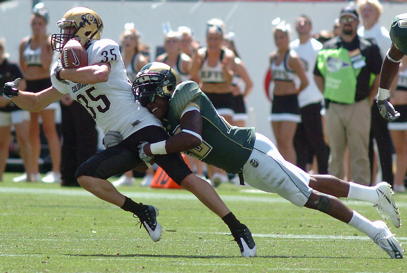 University of Colorado wide receiver Kyle Cefalo is tackled by Colorado State's Elijah-Blu Smith after making a catch in the third quarter of their game Saturday at Invesco Field in Denver.