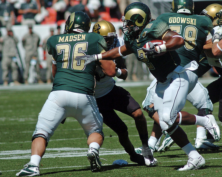 Colorado State University running back Leonard Mason makes a carry behind the block of lineman Paul Madsen in the third quarter of their game Saturday at Invesco Field in Denver.