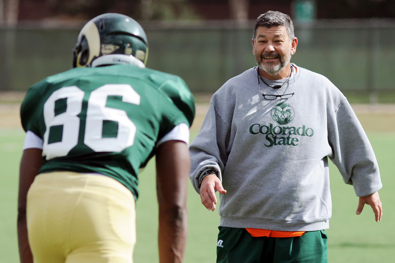 Colorado State University tight ends coach Art Valero works with Kivon Cartwright during practice Friday, April 5, 2013 at the team's on-campus practice field.
