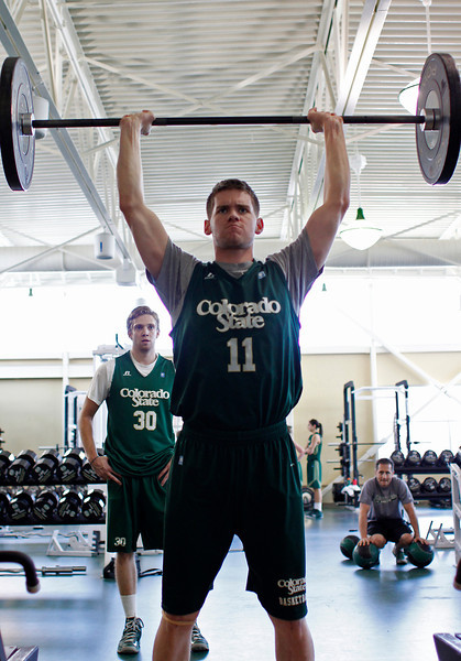 CSU men's basketball senior guard Jesse Carr performs an overhead press while sophomore guard Josh Morgan looks on Tuesday afternoon, during an off-season workout at the CSU Academic and Training Center in Fort Collin.