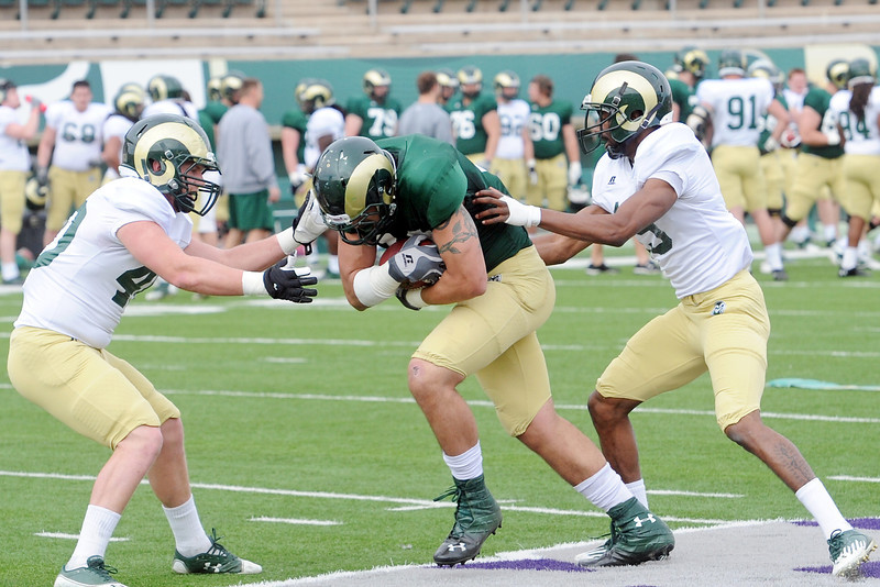 Colorado State University linebacker Max Morgan, left, and defensive back DeAndre Elliott, right, converge on tight end Crockett Gillmore after he made a catch during a drill before their intra-squad scrimmage Saturday, April 6, 2013 at Hughes Stadium in Fort Collins, Colo.