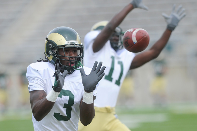 Colorado State University defensive back Shaq Bell (3) makes a catch while working on a drill with teammate Ousman Ba (11) prior to an intra-squad scrimmage on Saturday, April 6, 2013 at Hughes Stadium in Fort Collins, Colo.
