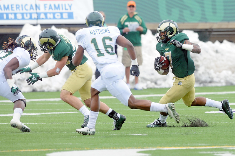 Colorado State University running back Donnell Alexander, right, runs behind the block of wide receiver Joe Hansley, second from left, while being pursued by defenders Jasen Oden, left, and Trent Matthews (16) during their scrimmage Saturday, April 20, 2013 at Hughes Stadium in Fort Collins, Colo.