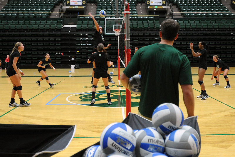 Colorado State assistant volleyball coach Matt Botsford, front, looks on while players work on a drill during practice Wednesday, Aug. 8, 2012 at Moby Arena.