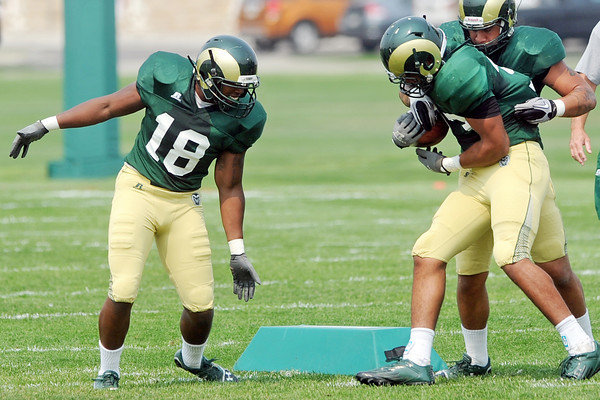 Colorado State linebacker Davis Burl, left, works on a drill with teammates Nu'uvali Fa'apito, right, and Kevin Davis during a recent practice at the team's on-campus practice field in Fort Collins.