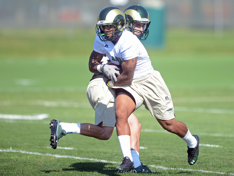 Colorado State running back Donnell Alexander, front, takes a handoff from quarterback Garrett Grayson during a recent practice.