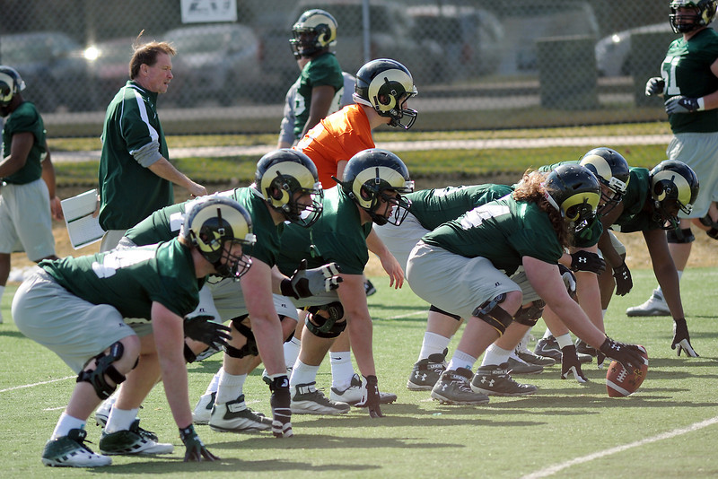 Colorado State University quarterback Garrett Grayson, middle in orange jersey, prepares to take a snap while working on a drill with teamates during football practice Wednesday, March 27, 2013 on-campus in Fort Collins, Colo.