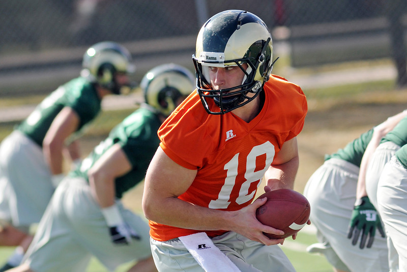 Colorado State University quarterback Garrett Grayson (18) drops back after taking the snap before handing the ball off while working on a drill during football practice Wednesday, March 27, 2013 on-campus in Fort Collins, Colo.