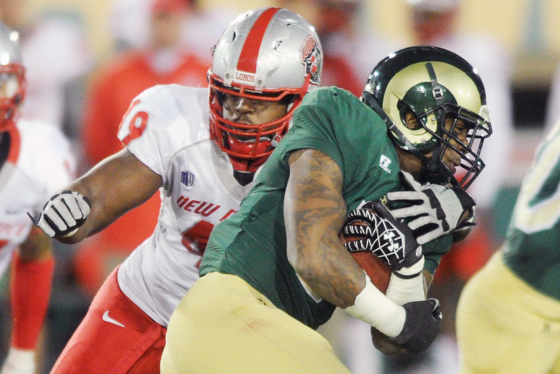 Colorado State running back Donnell Alexander, front, is tackled by New Mexico defender Ugo Uzodinma in the second quarter of their game on Saturday, Nov. 24, 2012 at Hughes Stadium.