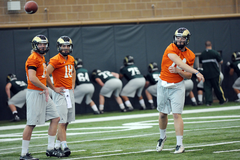 Colorado State's M.J. McPeek, right, throws a pass while fellow quarterbacks Conner Smith, right, and Garrett Grayson look on during practice Tuesday, Oct. 16, 2012 at the team's on-campus indoor practice facility in Fort Collins.