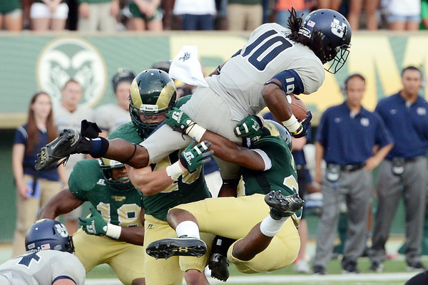Utah State University wide receiver Chuck Jacobs (10) is tackled by Colorado State's Aaron Davis, right, and Max Morgan in the second quarter of their game on Saturday, Sept. 22, 2012 at Hughes Stadium in Fort Collins.