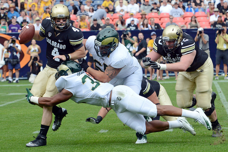 Colorado quarterback Jordan Webb, left, is sacked by Colorado State defenders Cory James, bottom, and Alex Tucci in the first quarter of their game Saturday, Sept. 1, 2012 at Sports Authority Field at Mile High.