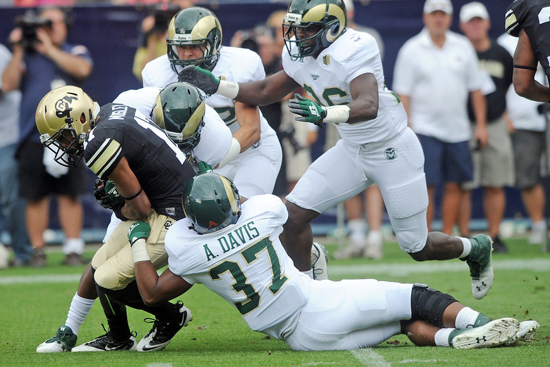 Colorado's Marques Mosley, left, is tackled by a host of Colorado State defenders on a kickoff return in the first quarter of their game Saturday, Sept. 1, 2012 at Sports Authority Field at Mile High. (Steve Stoner/Loveland Reporter-Herald)