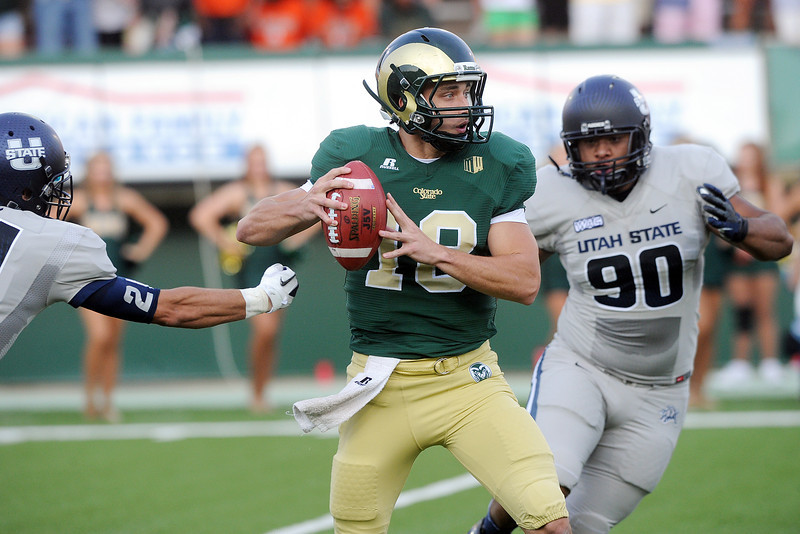 Colorado State University quarterback Garrett Grayson (18) attempts to avoid Utah State defenders Brian Suite, left, and Al Lapuaho on a pass play in the first quarter of their game on Saturday, Sept. 22, 2012 at Hughes Stadium in Fort Collins.