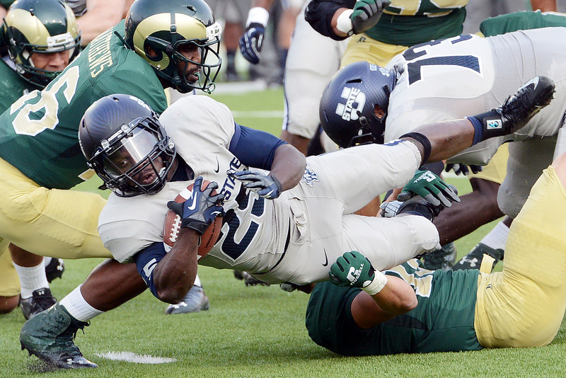 Utah State University running back Kerwynn Williams (25) is tackled Colorado State's Trent Matthews, left, and Austin Gray, bottom, on a run play in the first quarter of their game on Saturday, Sept. 22, 2012 at Hughes Stadium in Fort Collins.