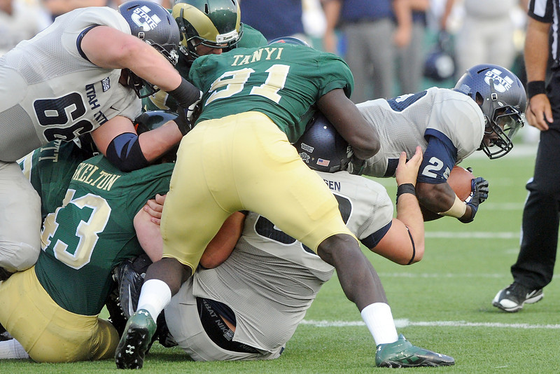 Utah State University running back Kerwynn Williams, right, stretches forward as he's tackled on a run play in the second quarter of a game against Colorado State on Saturday, Sept. 22, 2012 at Hughes Stadium in Fort Collins.