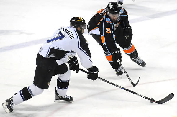 Colorado Eagles defenseman Joe Grimaldi, left, chases down the puck in front of Missouri Mavericks defenseman Ray DiLaurothe first period of their game Friday, April 15, 2011 at the Budweiser Events Center in Loveland, Colo.