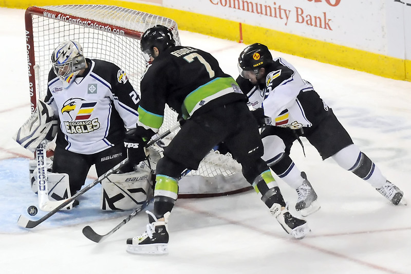 Quad-City Mallard forward Jake Riddle attempts to get the puck past Colorado Eagles goalie Kyle Jones and defenseman Kyle Peto in the first period of their game Saturday, April 2, 2011 at the Budweiser Events Center in Loveland, Colo.