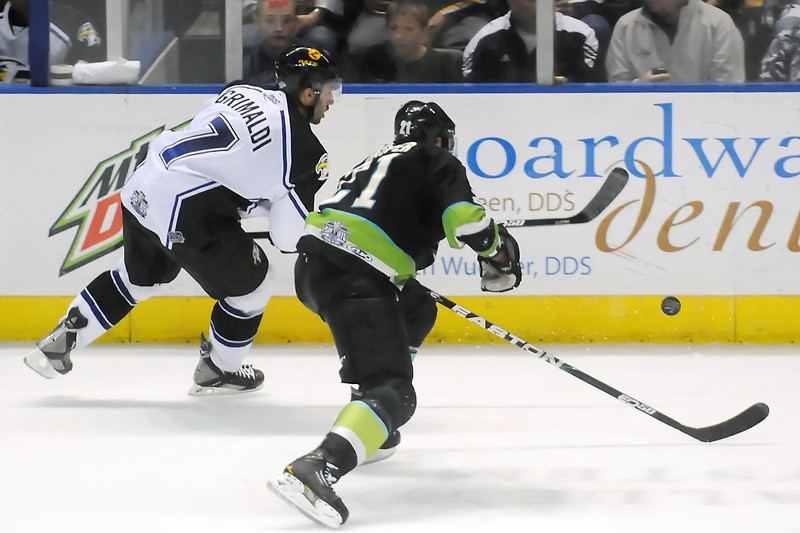 Colorado Eagles defenseman Joe Grimaldi (7) and Quad-City Mallards center Joel Gasper track down the puck against the boards in the second period of their game Saturday, April 2, 2011 at the Budweiser Events Center.