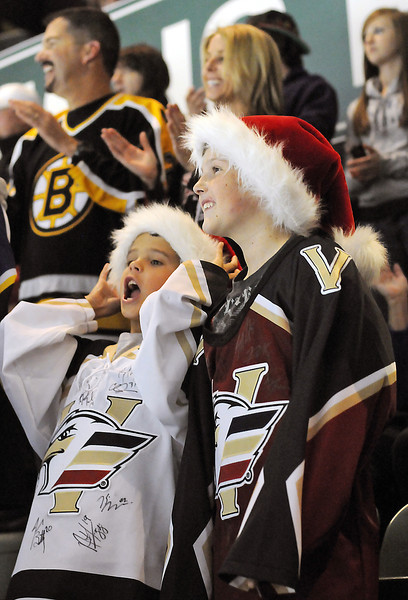 Quincy Marcotte, 12, right, and his brother, Roman, 10, don festive Santa hats as they cheer on the Colorado Eagles during their hockey game against the Arizona Sundogs on Wednesday night at the Budweiser Events Center.
