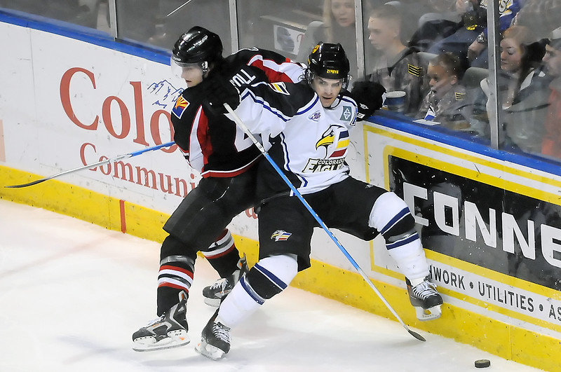 Colorado Eagles winger Kevin Ulanski, right, and Arizona Sundogs defenseman Jim Driscoll battle against the boards for control of the puck in the first period of their game Wednesday night at the Budweiser Events Center.