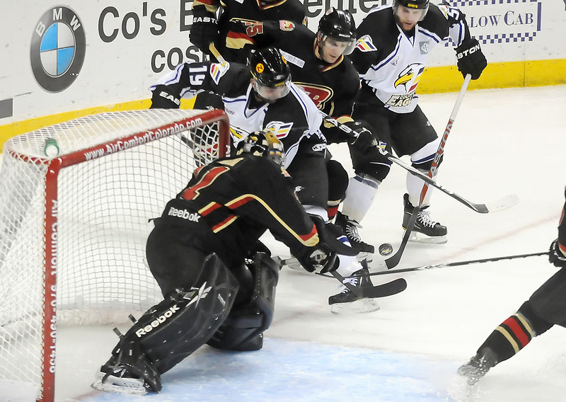 Colorado Eagles teammates Dylan Stanley, right, and Adam Hogg battle for the puck against Rapid City Rush goalie Tim Boron and defenseman Scott Kalinchuk in the first period Wednesday at the Budweiser Events Center.