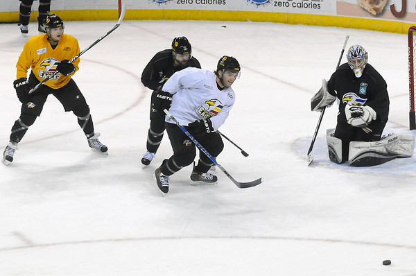 Colorado Eagles goalie Kyle Jones works on a drill with teammates, from left to right, Adam Cherneyko, Brett Thurston and Kevin Ulanski during practice Wednesday at the Budweiser Events Center.