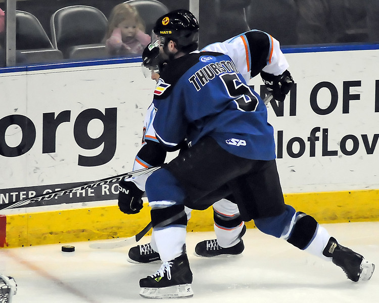 Colorado Eagles defenseman Brett Thurston (5) battles for the puck behind the net against Missouri Mavericks forward Derek Pallardy in the first period of their game Wednesday at the Budweiser Events Center.