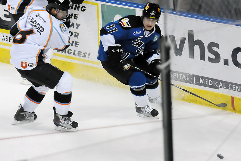 Colorado Eagles forward Matt Glasser (11) tracks down the puck in front of Missouri Mavericks defenseman Jared Lavender in the first period of their game Wednesday at the Budweiser Events Center.