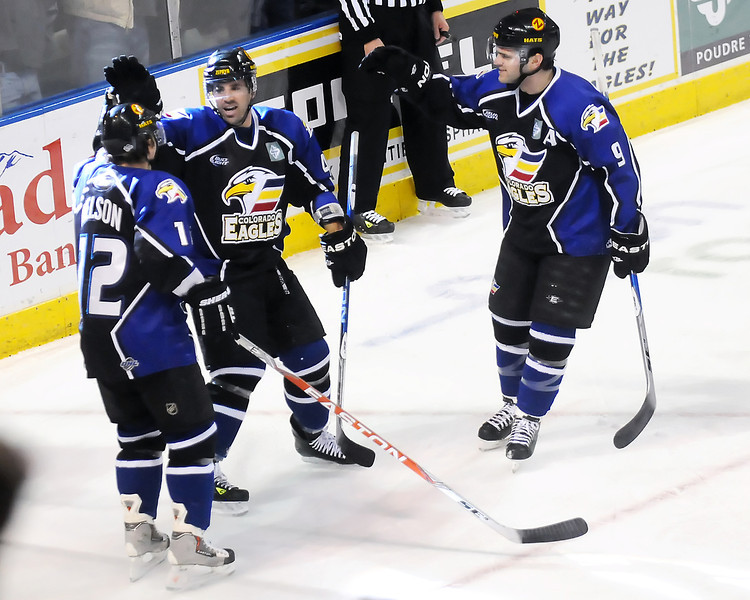 Colorado Eagles forward Scott May, center, is congratulated by teammates Riley Nelson, left, and Kevin Ulanski after May scored a goal in the second period of a game against the Rapid City Rush on Wednesday, Feb. 23, 2011 at the Budweiser Events Center.