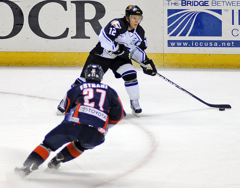 Riley Nelson of the Colorado Eagles passes before Kevin Estrada can disrupt the action during the first period of Saturday night's game at the Budweiser Events Center.