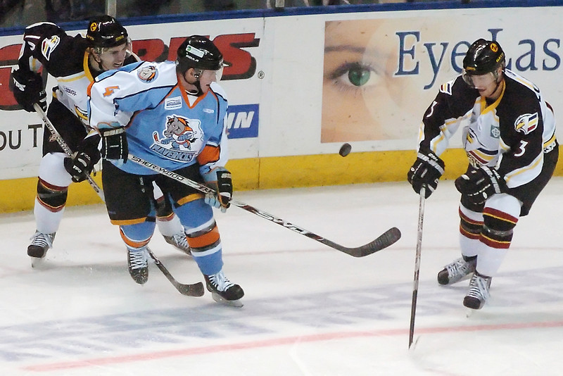 Colorado Eagles teammates Steve Haddon, left, and Jason Lundmark battle for the puck with Missouri Mavericks defenseman Tyler Bret in the first period of their game on Saturday, Dec. 19, 2009 at the Budweiser Events Center.