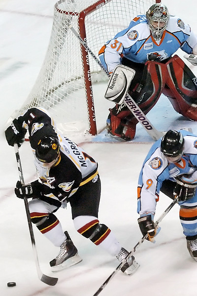 Colorado Eagles center Ed McGrane chases down the puck in front of Missouri Mavericks goalie Alexandre Vincent and center Chad Hinz in the first period of their game on Saturday, Dec. 19, 2009 at the Budweiser Events Center.