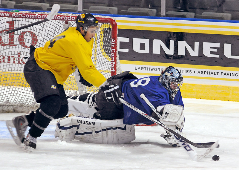 Colorado Eagles goalie Andrew Penner stretches to for control of the puck as forward Derek Hansberry battles with him during the team's first practice on Monday at the Budweiser Events Center in Loveland.