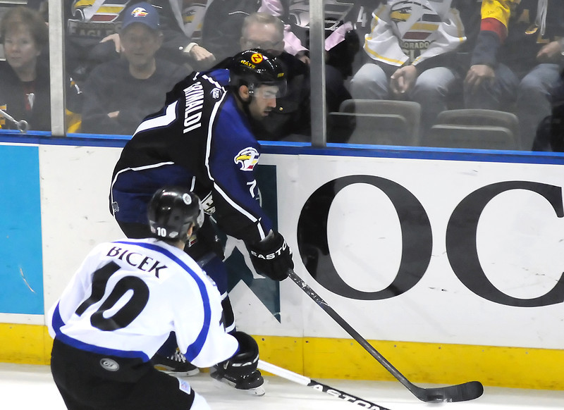 Colorado Eagles defenseman Joe Grimaldi skates with the puck in front of Evansville Icemen forward Brian Bicek during their game last week at the Budweiser Events Center.