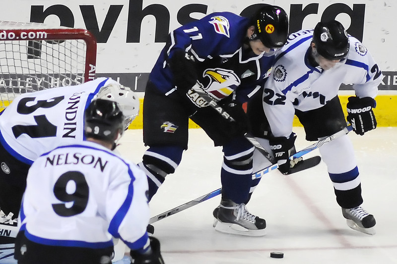 Colorado Eagles forward Matt Glasser, center, battles for the puck with Evansville Icemen defenseman Nick Schneider (22) while goalie Matt Lundin and Jeff Nelson look on in the second period of their game Wednesday at the Budweiser Events Center.
