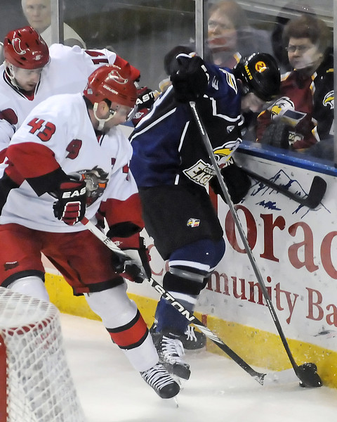 Colorado Eagles defenseman Aaron Schneekloth, right, battles against the boards with Odessa Jackalopes players Mike Ramsay, left, and Sebastien Thinel in the first period Saturday, Jan. 15, 2011 at the Budweiser Events Center.
