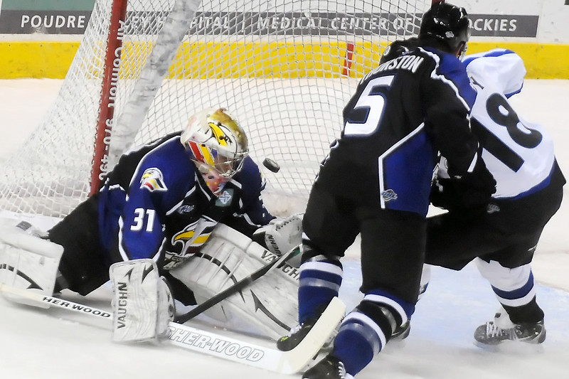 Evansville Icemen winger Mark Cody, right, slips the puck past Colorado Eagles goalie Andrew Penner while defenseman Brett Thurston looks on in the first period of their game Wednesday at the Budweiser Events Center. The Eagles lost, 3-2.