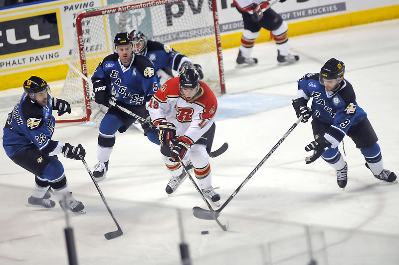 Colorado Eagles players Aaron Schneekloth (23), Brett Thurston (5) and Kevin Ulanski (9) track down the puck against Rapid City Rush forward Derek LeBlanc in the second period of their game on Sunday, Feb. 28, 2010 at the Budweiser Events Center.