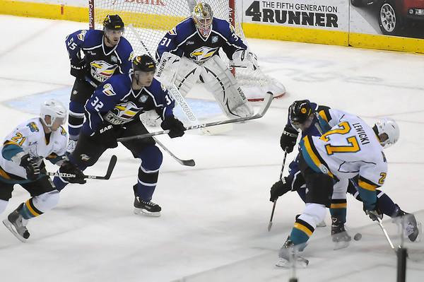 Rio Grande Valley Killer Bees forward Aaron Lewicki, right, battles for the puck against Colorado Eagles center Adam Hogg while Tomas Klempa (21), Alex Penner (32), Kyle Peto (55) and goalie Andrew Penner look on in the first period of their game Friday at the Budweiser Events Center.