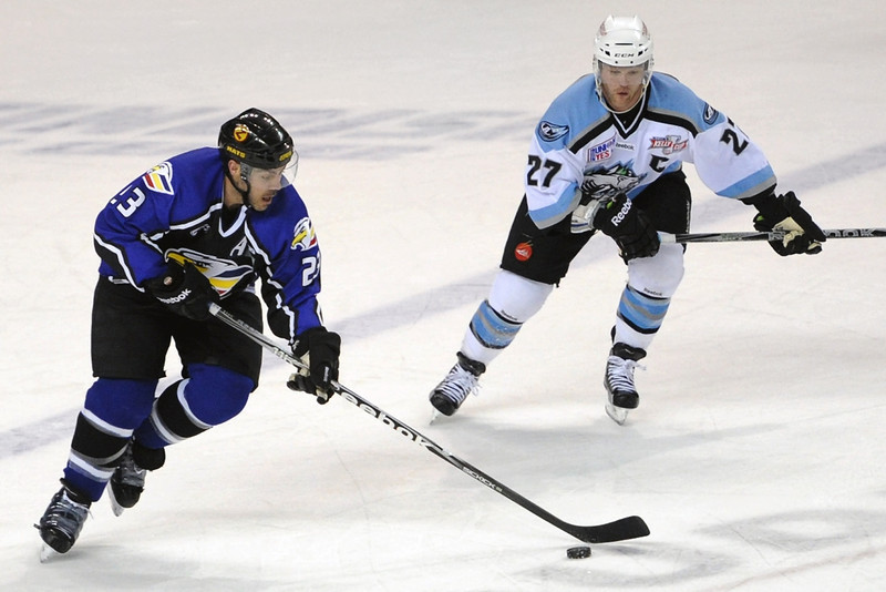 Colorado Eagles defenseman Aaron Schneekloth, left, skates around Alaska Aces center Brian Swanson in the first period of their game on Friday, March 16, 2012 at the Budweiser Events Center.