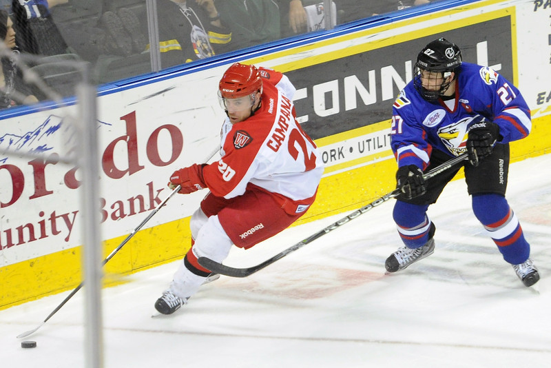 Colorado Eagles forward Dylan Hood, right, battles along the boards with Las Vegas Wranglers defenseman Matt Campanale in the first period of their game on Wednesday, March 13, 2013 at the Budweiser Events Center.