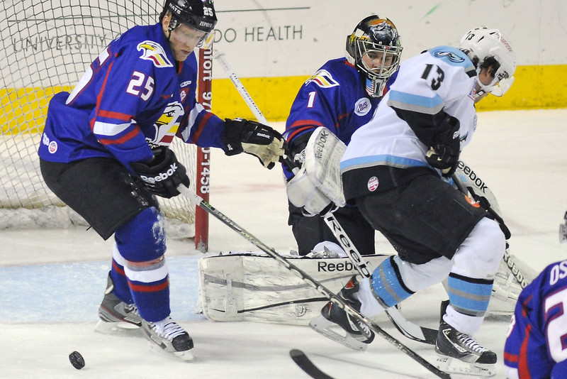 Colorado Eagles defenseman Jake Marto, left, and goalie Adam Brown work in front of the net against Alaska Aces forward Evan Trupp in the first period of their game on Wednesday, March 20, 2013 at the Budweiser Events Center.