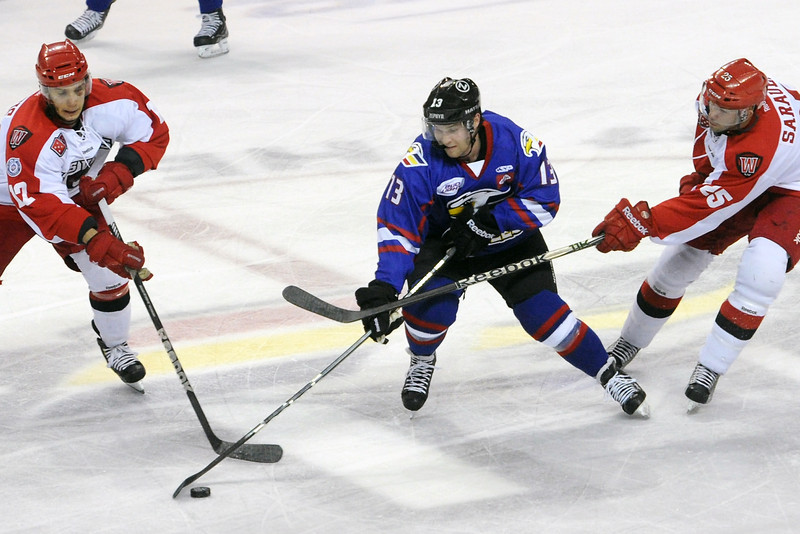 Colorado Eagles forward Chad Costello, middle, tracks down the puck between Las Vegas Wranglers players Chris Francis, left, and Andrew Sarauer in the first period of their game on Wednesday, March 13, 2013 at the Budweiser Events Center.